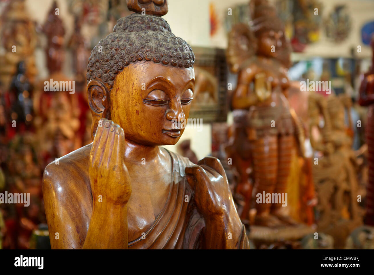 Sri Lanka - traditional wood carving, shop with wooden souvenirs, detail of buddha statue - Stock Image