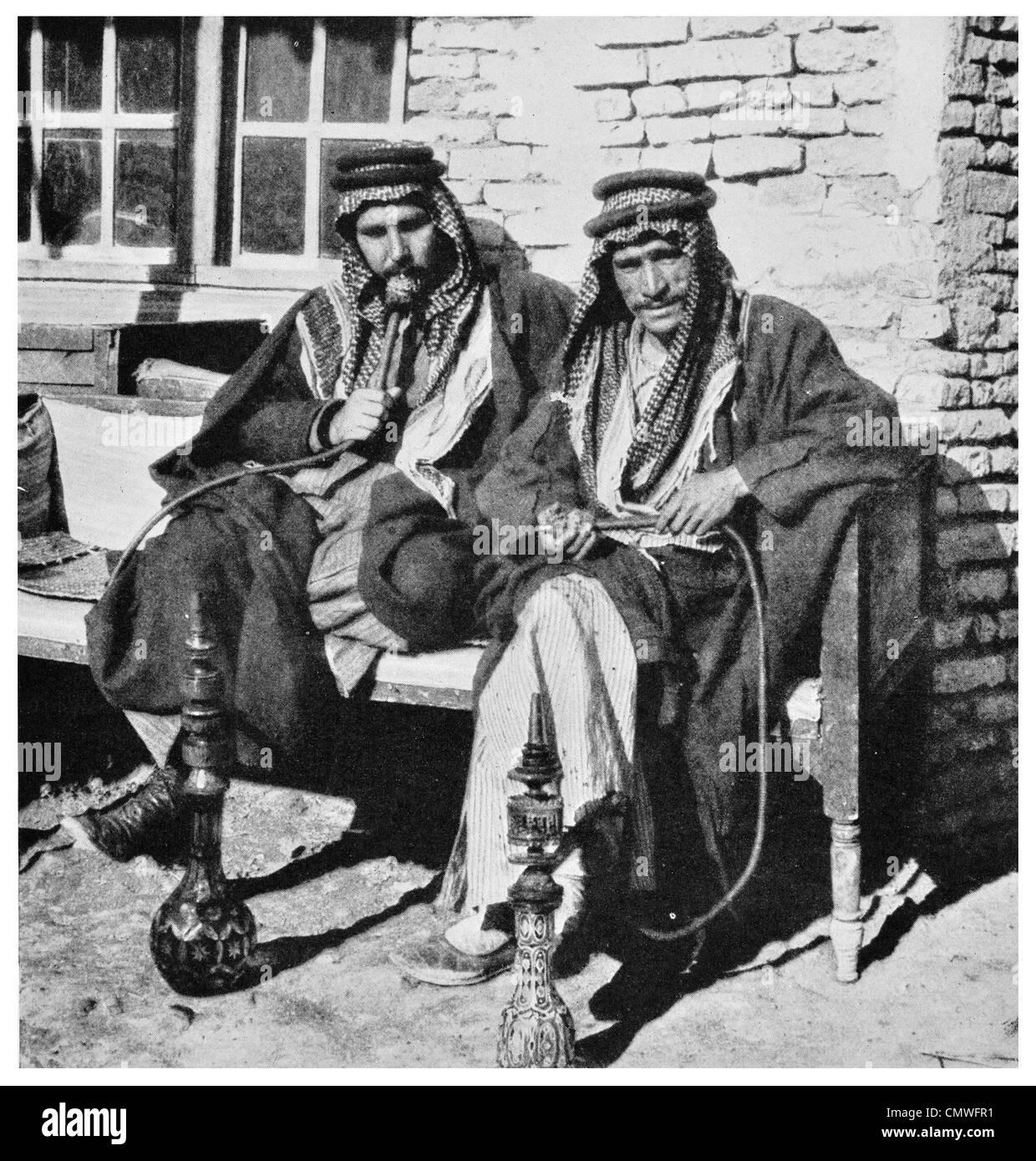 1925 desert Arabs of high degree smoking the water pipe Narghile coffee shop - Stock Image