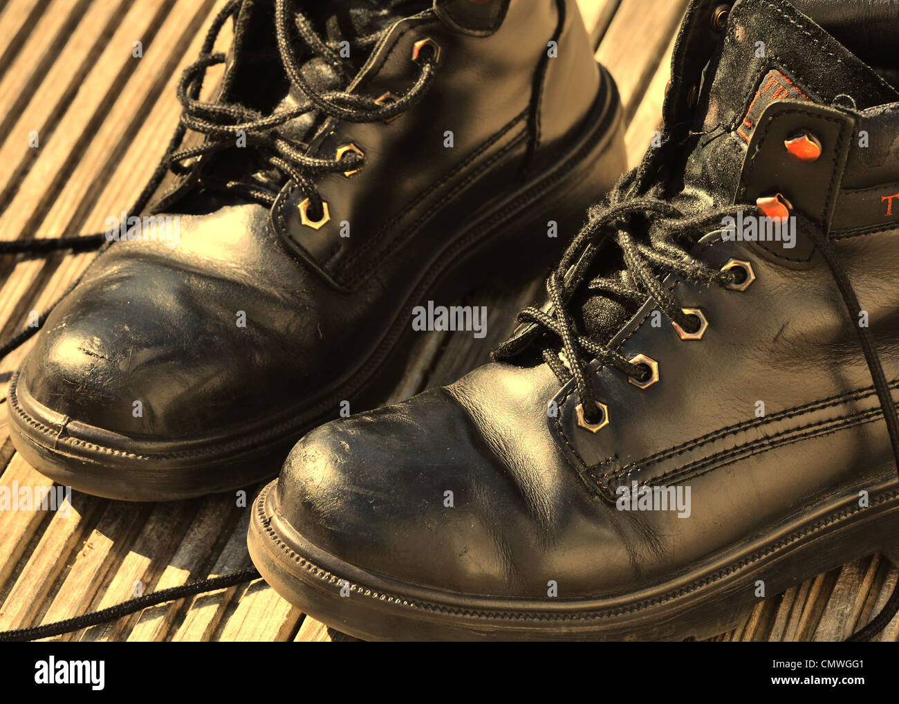 A pair of old black boots in sepia tones - Stock Image