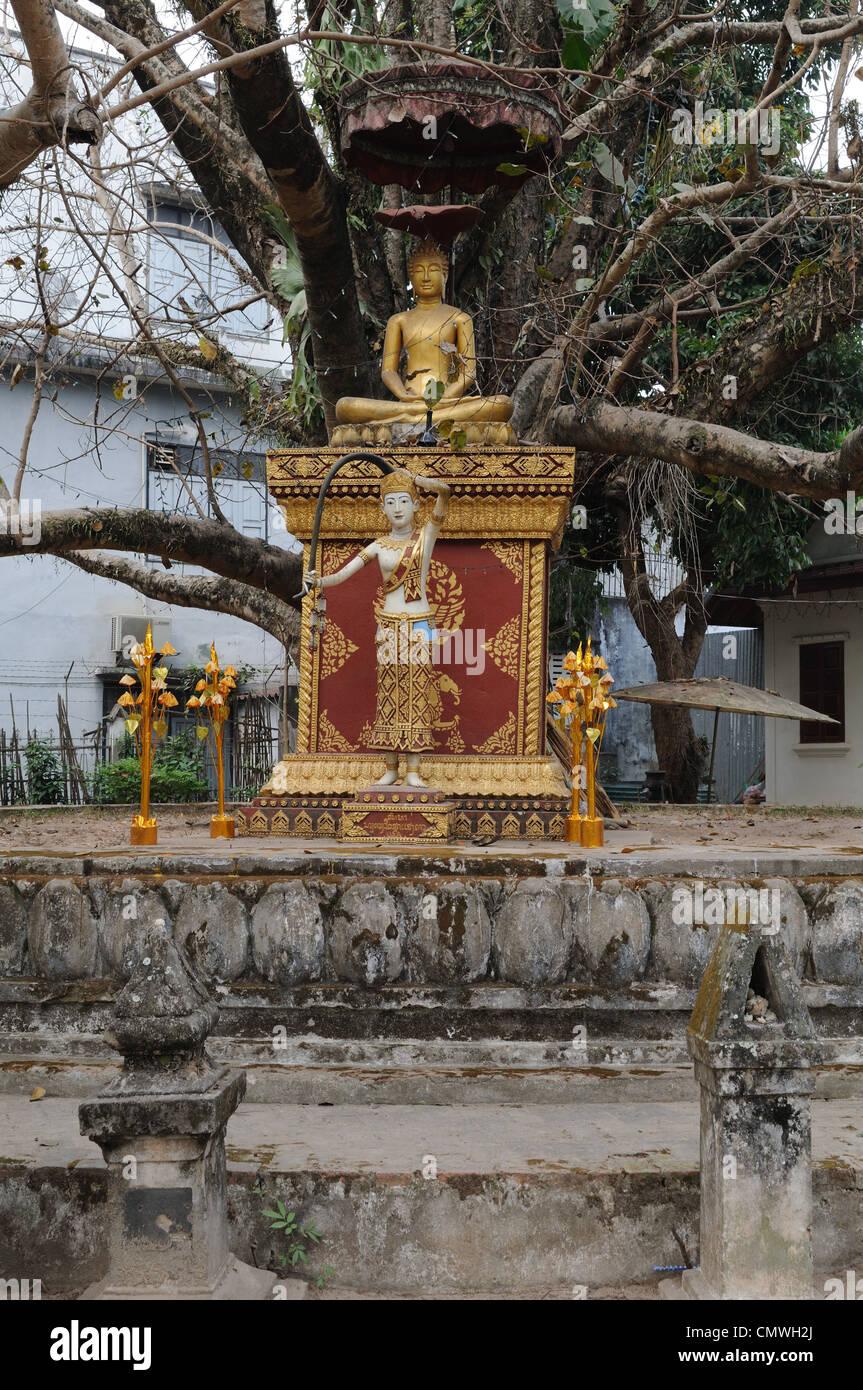 Statues of Buddha and Buddhist Earth Mother Goddess at Wat Visoun Luang Prabang laos - Stock Image