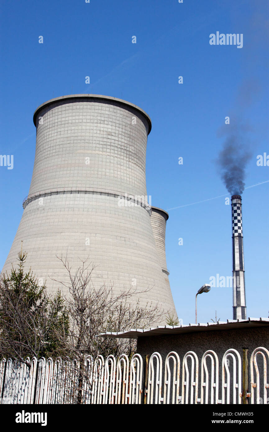 Cooling towers and chimney of Bobov Dol coal-fired power plant in western Bulgaria, black smoke coming out of the - Stock Image