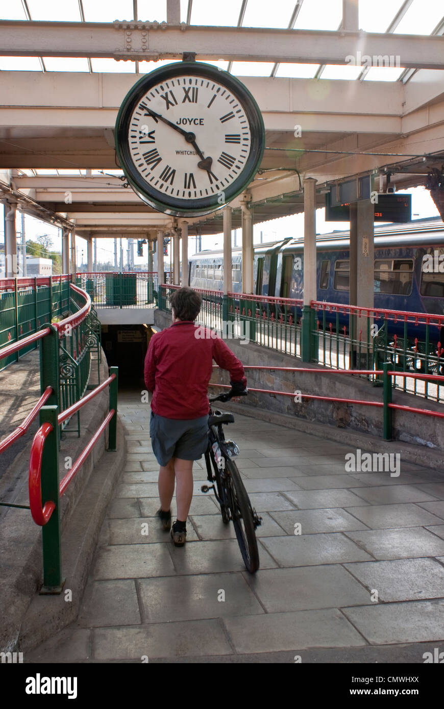 Woman with bicycle at Carnforth station Lancashire. Station and clock featured in the classic film Brief Encounter - Stock Image