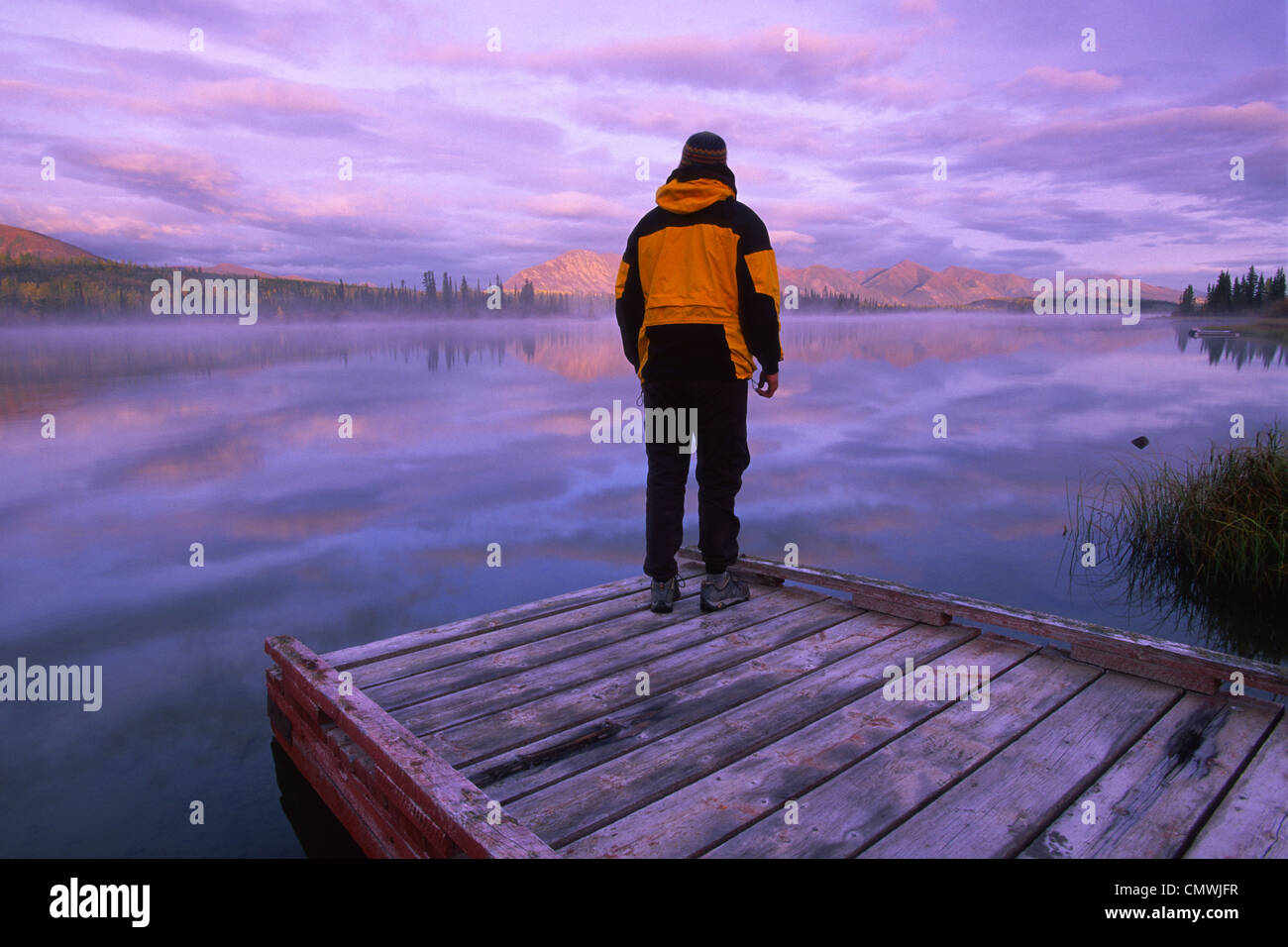 Hiker on Dock at Sunrise, Jackfish Lake, near confluence of North Canol and Robert Campbell Highways, south of Ross - Stock Image