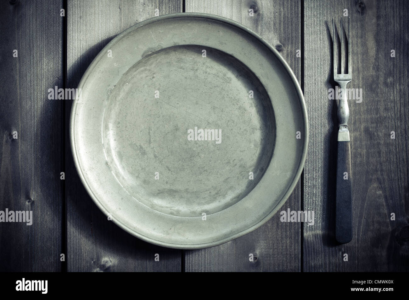 antique fork and plate on a wooden table - Stock Image