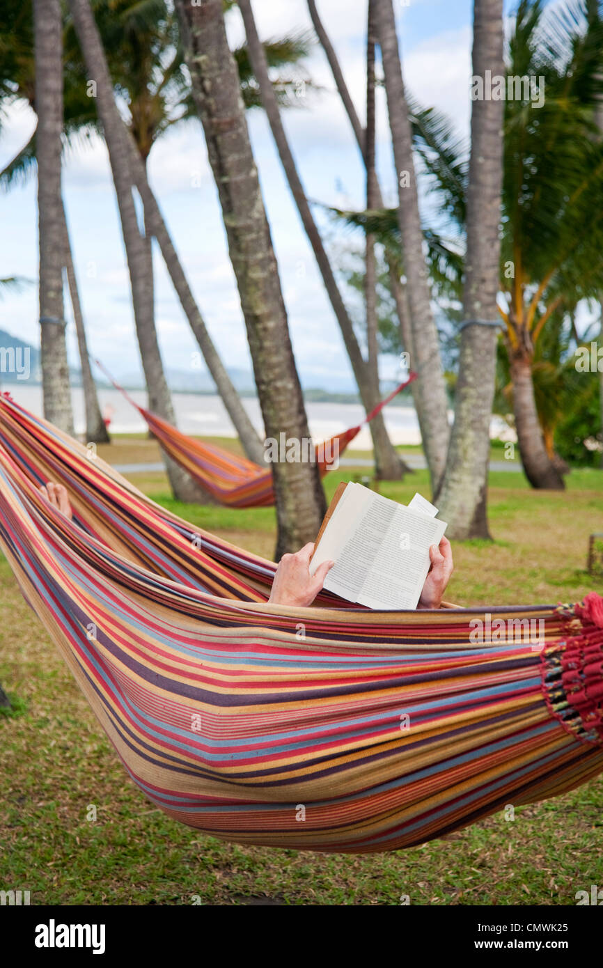 Man relaxing in hammock reading a book. Palm Cove, Cairns, Queensland, Australia - Stock Image