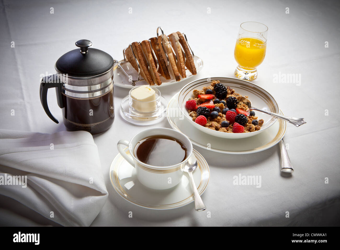 continental breakfast with coffee juice cereal and toast, laid out on a white linen tablecloth - Stock Image