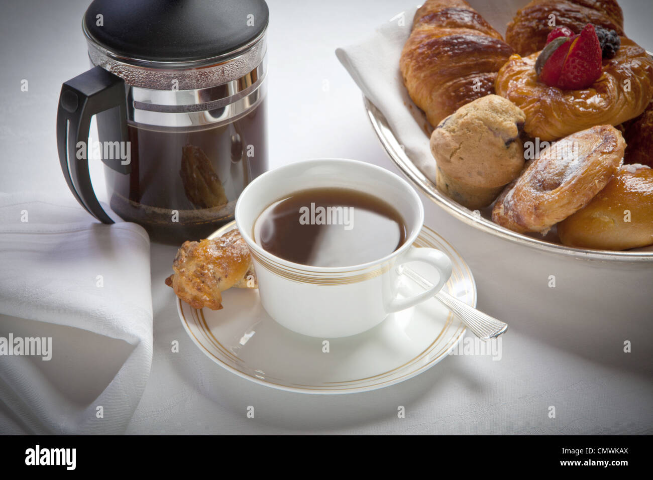 breakfast cup of white coffee and cafetiere and with pastries , laid out on a white linen tablecloth - Stock Image