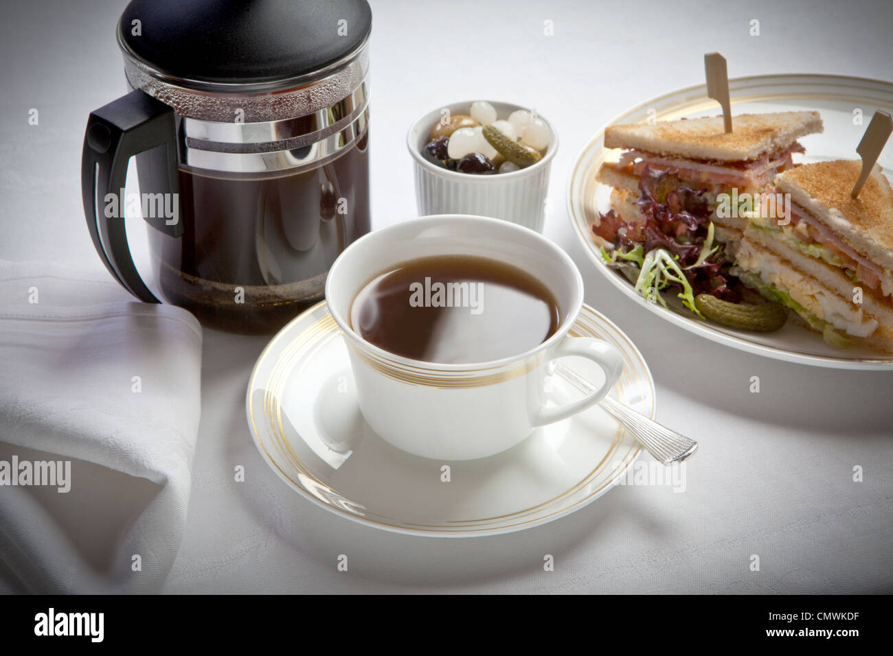 cup of black coffee with sandwiches, laid out on a white linen tablecloth - Stock Image