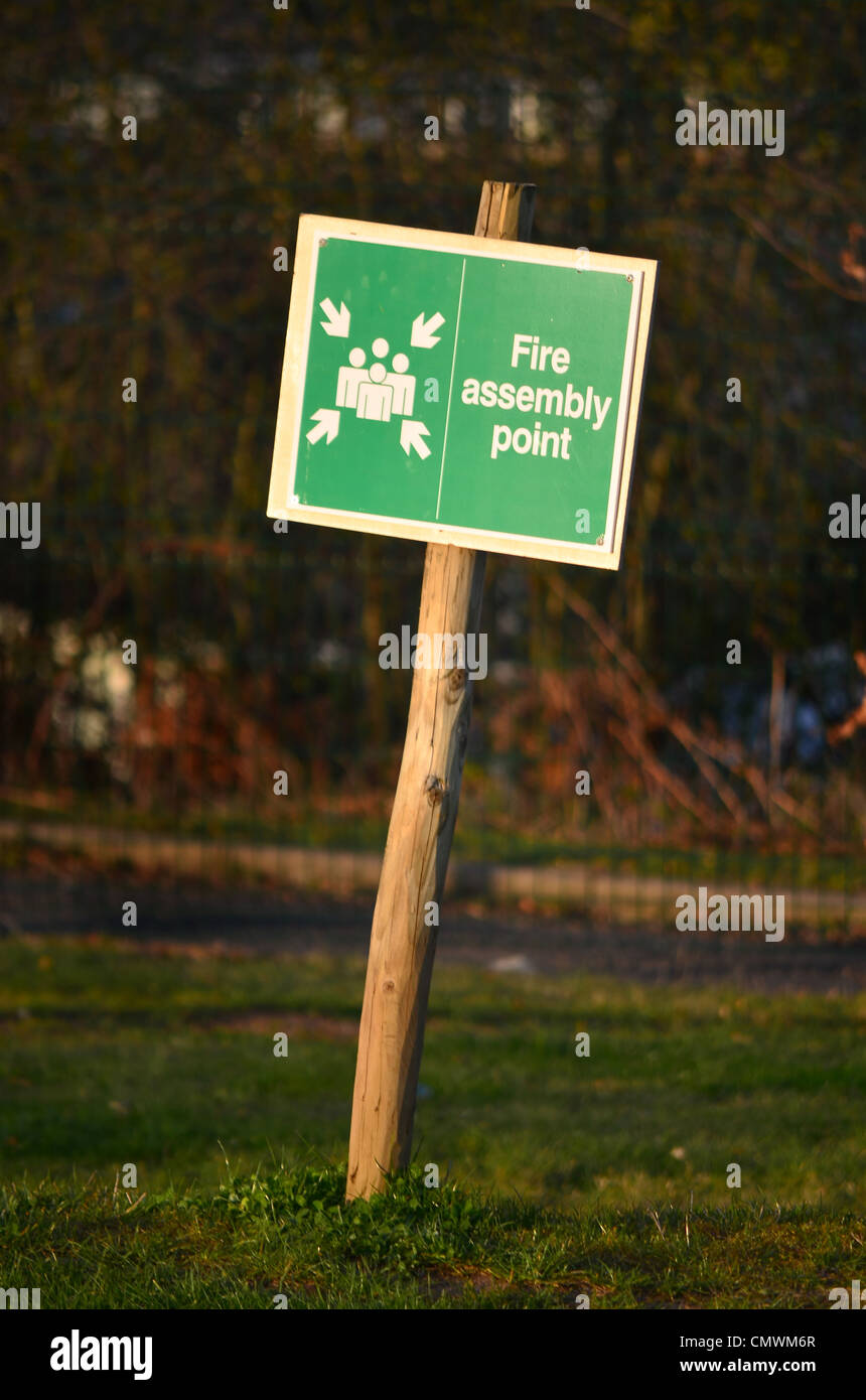 Fire assembly point sign on a wooden post at an angle - Stock Image