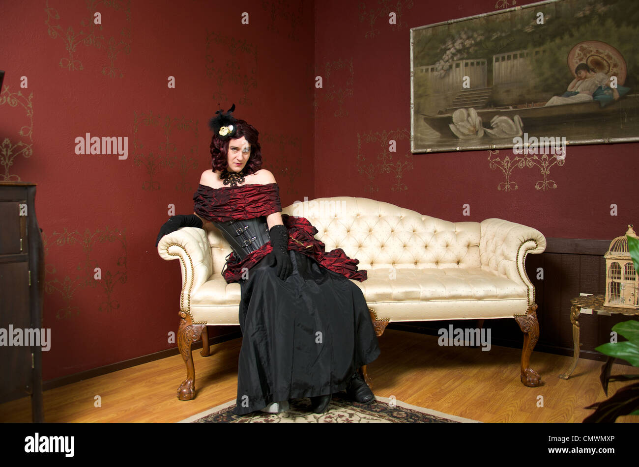 A lady dressed in victorian steampunk outfit on white couch. - Stock Image