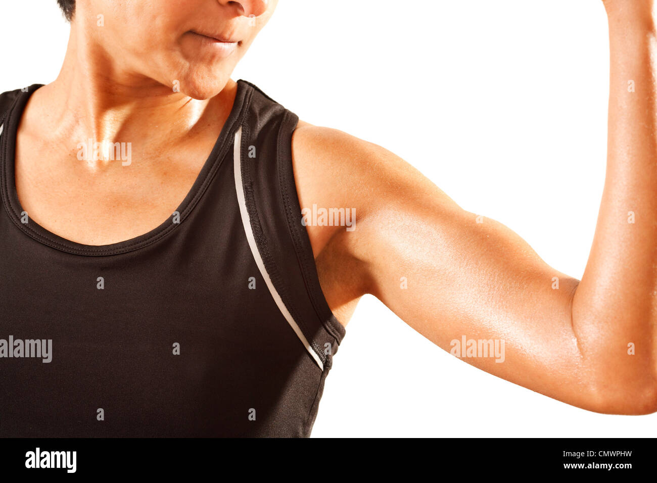 An athletic Asian Indian woman clenches her bicep. White background. Stock Photo
