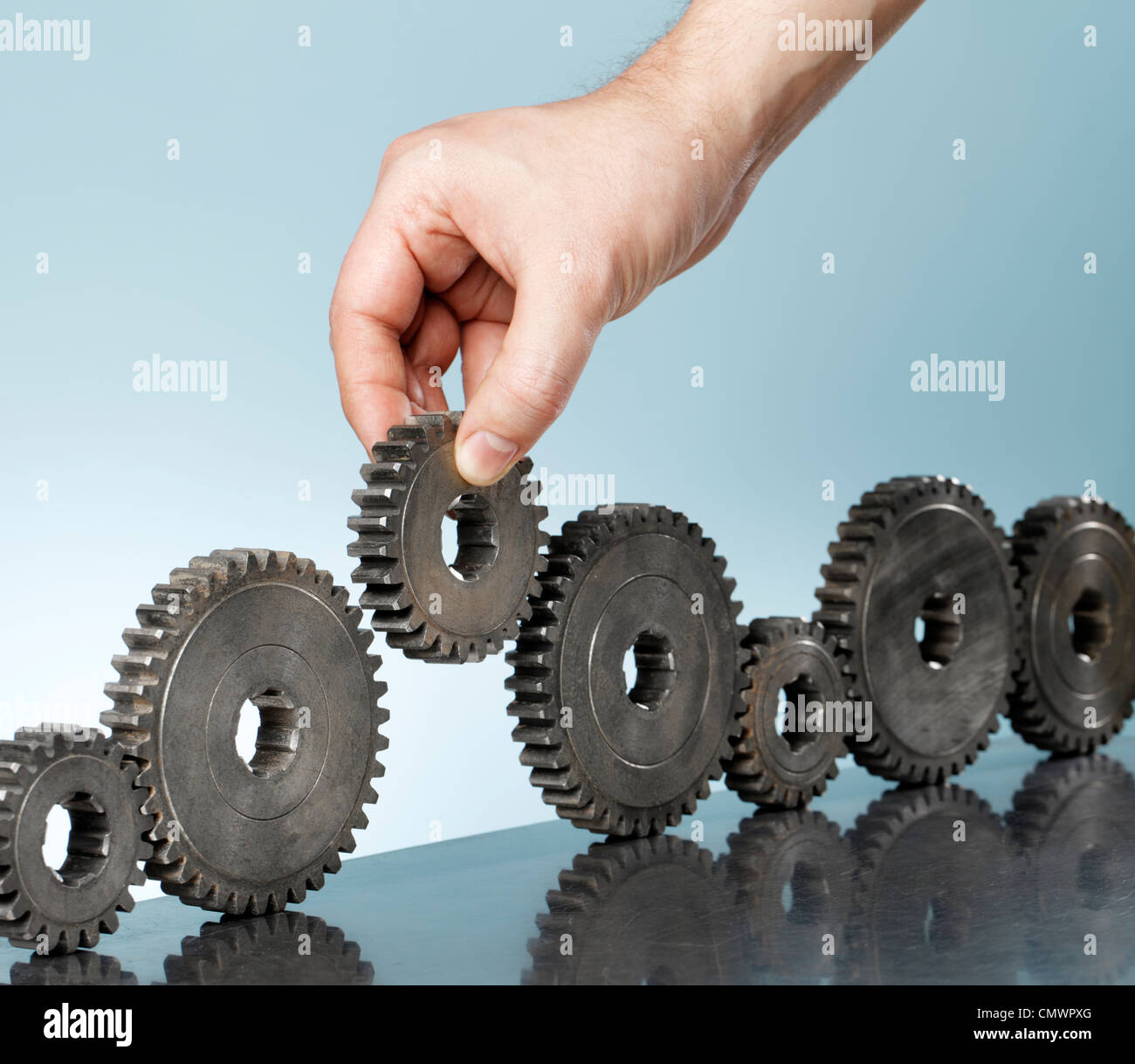 Man adding a cog gear in a row of old cog gears. - Stock Image