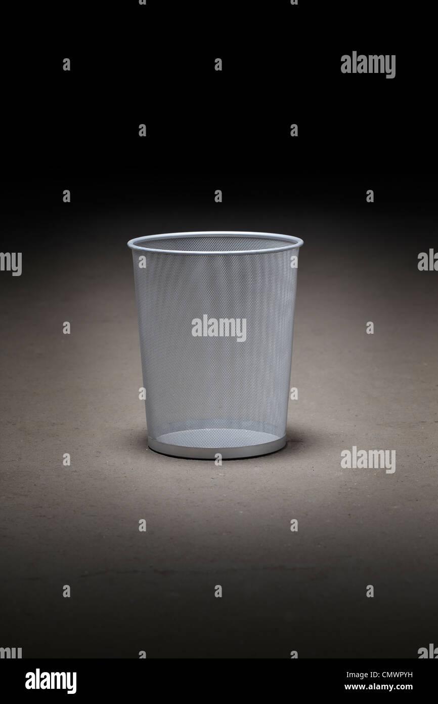 Empty wastepaper basket on dirty concrete floor. Stock Photo