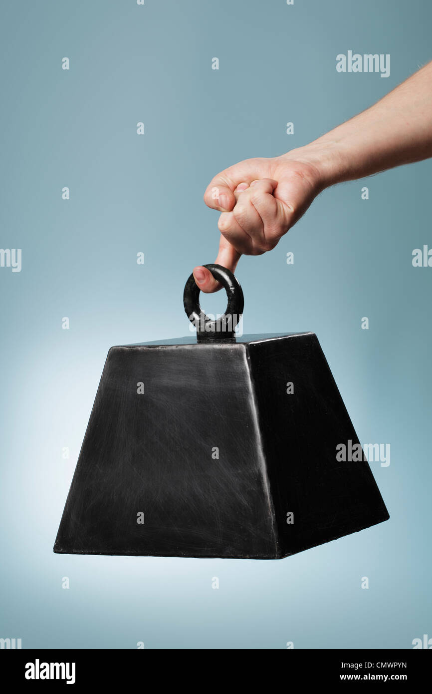 Man holding a seemingly heavy weight that is a fake prop. - Stock Image