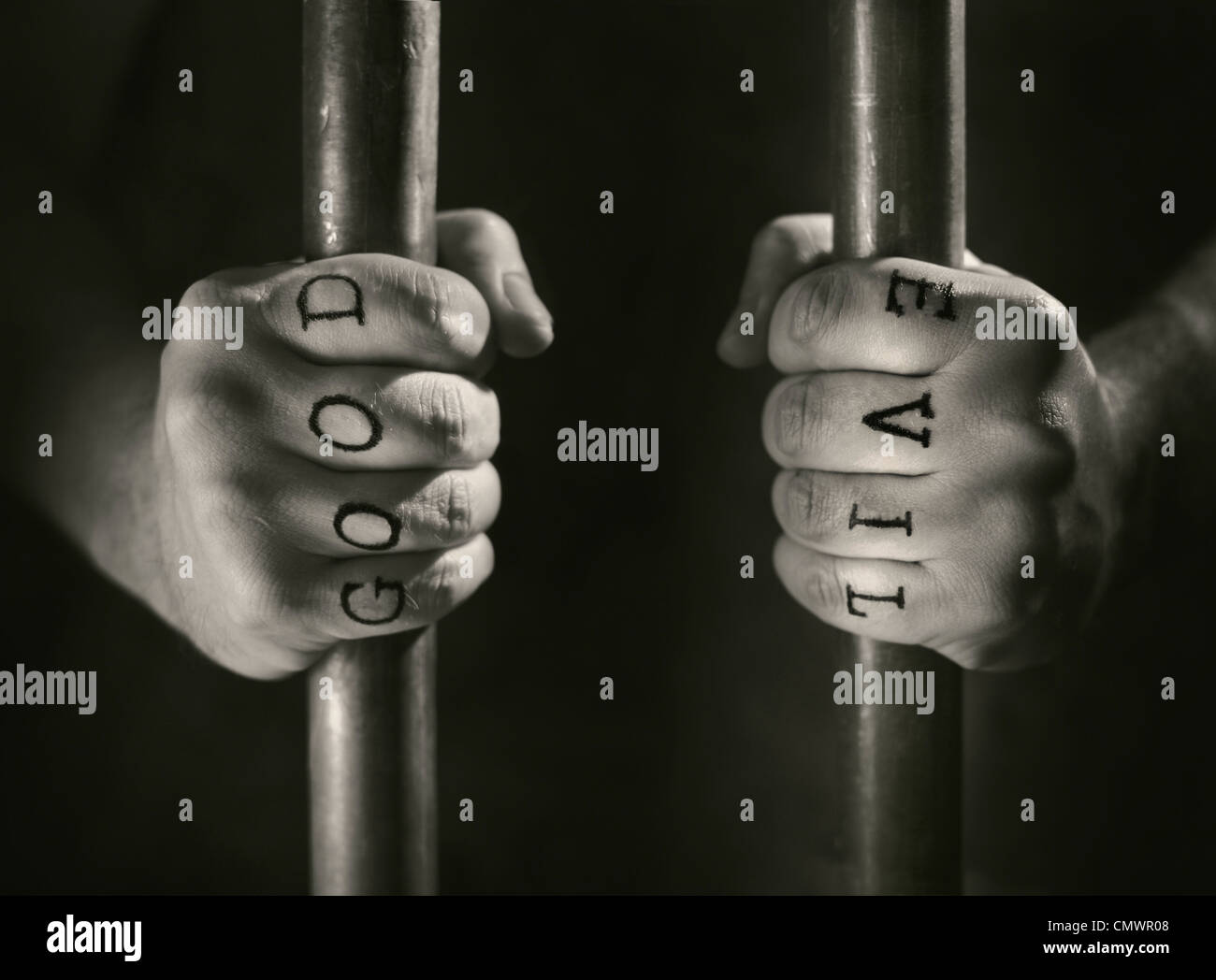 Man with (fake) Good and Evil tattoos behind prison bars. - Stock Image