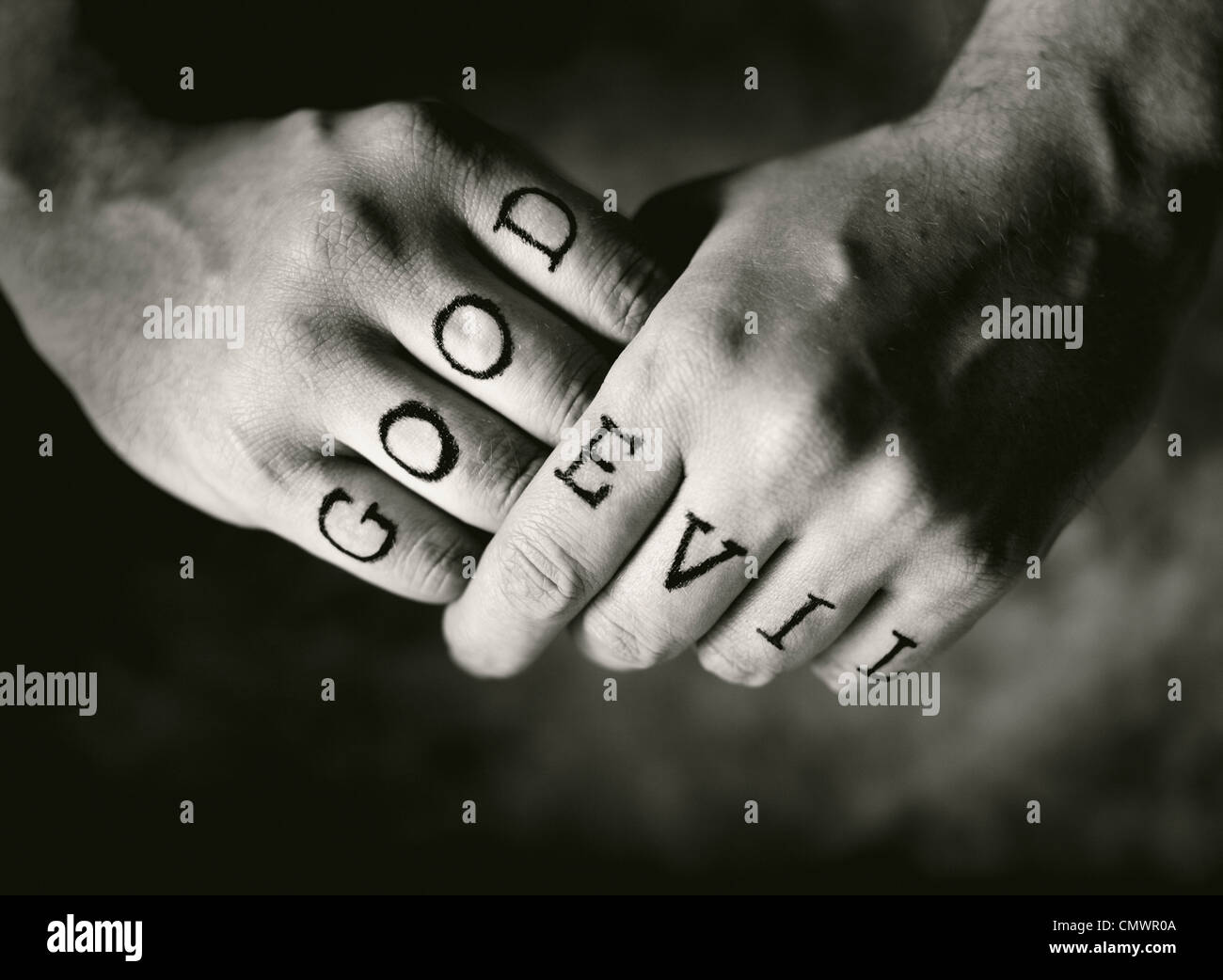 Man With Good And Evil Fake Tattoos On His Fingers Stock Photo