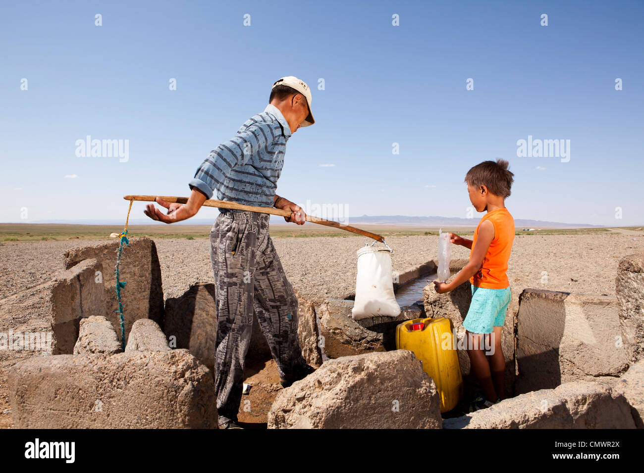 Father and son bail the well water in Gobi desert, Mongolia - Stock Image