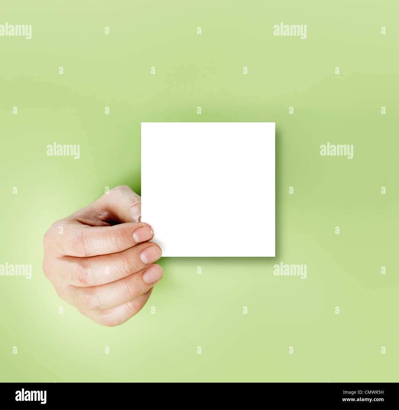A hand holding a blank note over green background. - Stock Image