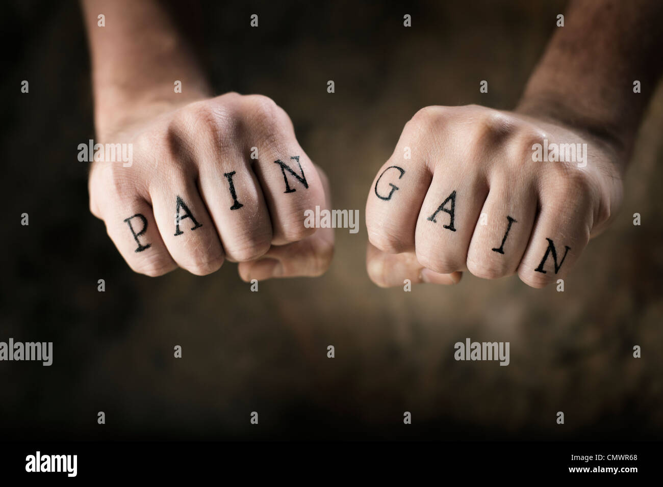 Man with fake tattoos 'Pain' and 'Gain' on his hands, referring to the exercise motto 'No Pain, - Stock Image