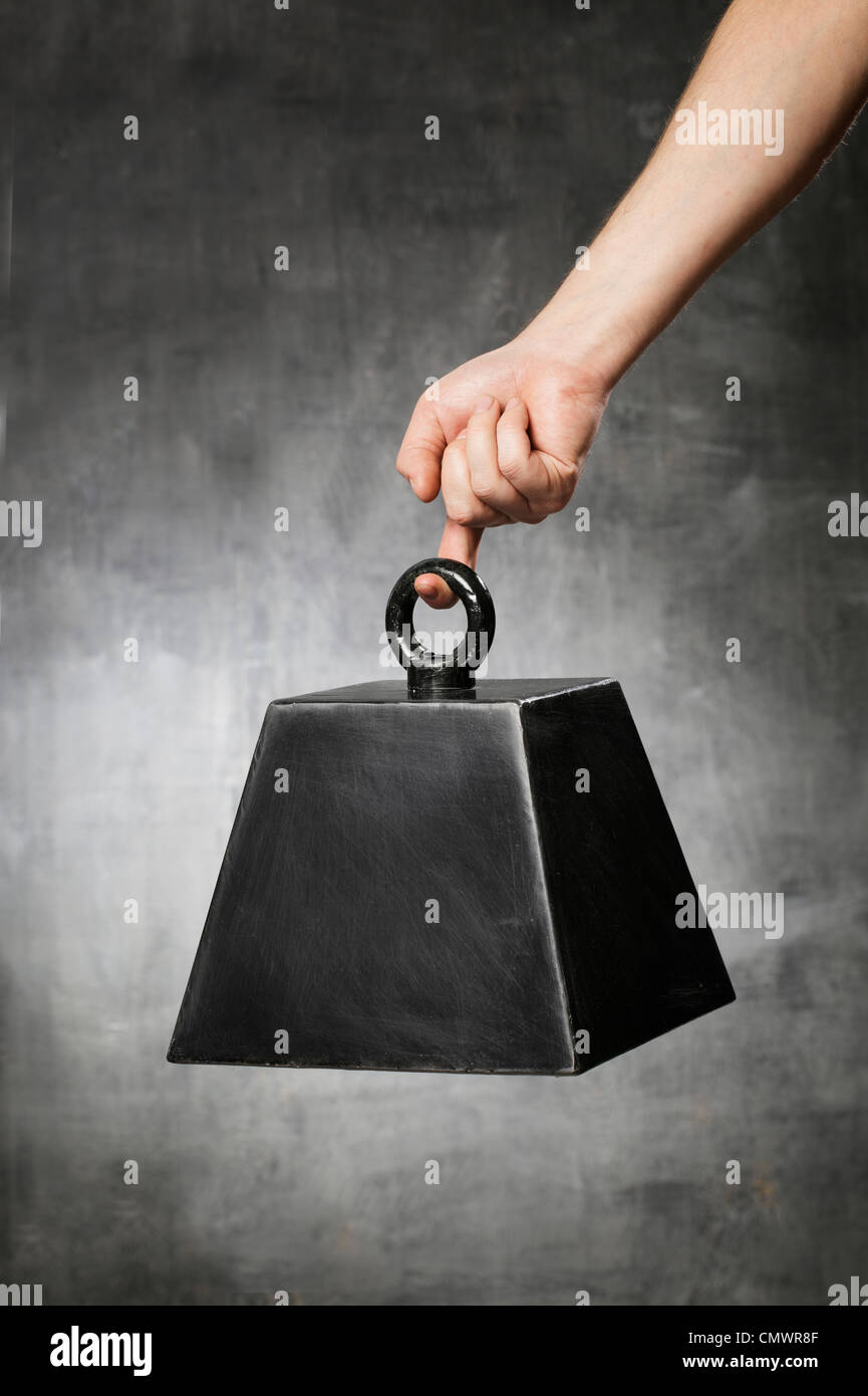 Man hanging a fake prop weight from his finger. - Stock Image