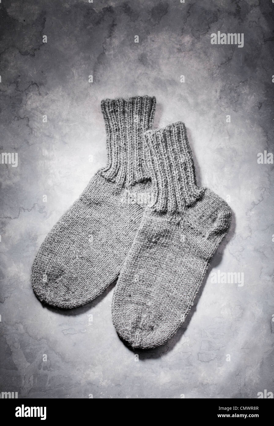 Hand-knitted grey wool socks on grey background Stock Photo