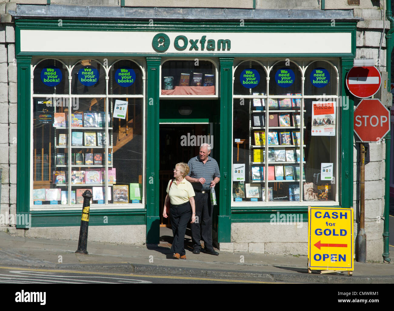 Senior man and woman, leaving Oxfam shop, in the town of Ulverston, Cumbria, England UK - Stock Image