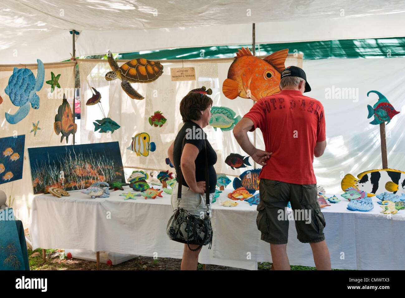 Couple shopping for handicrafts at Sunday Markets. Port Douglas, Queensland, Australia - Stock Image