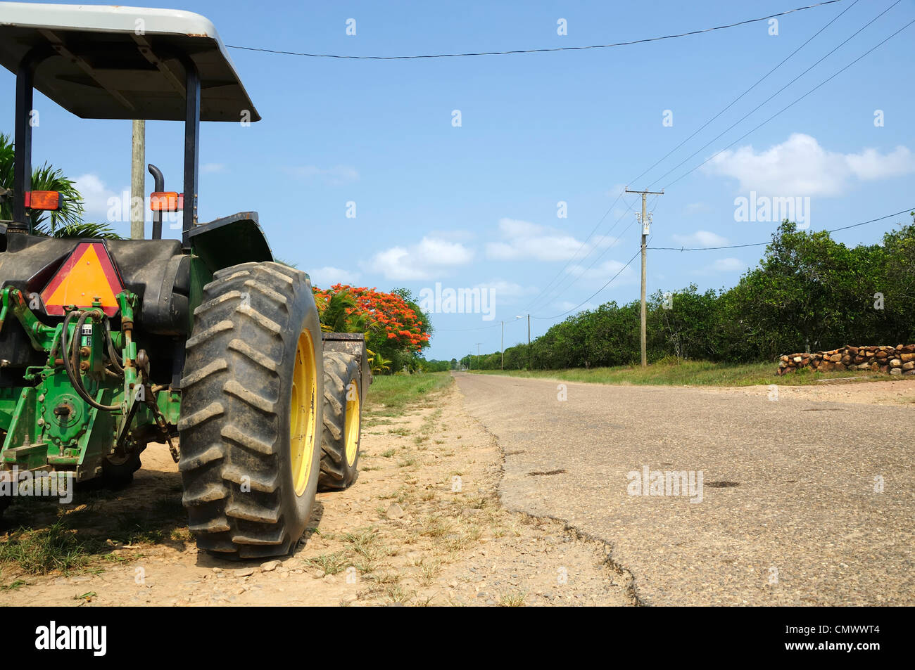 A tractor parked at the side of an empty road viewed from the rear. - Stock Image