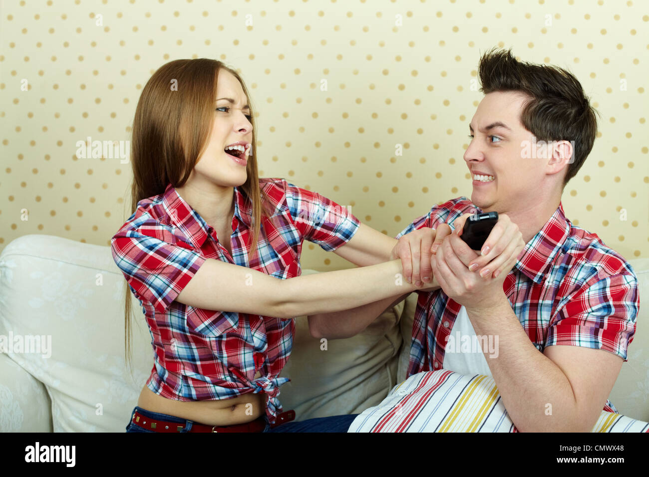 portrait of young couple fighting beacause of remote control stock