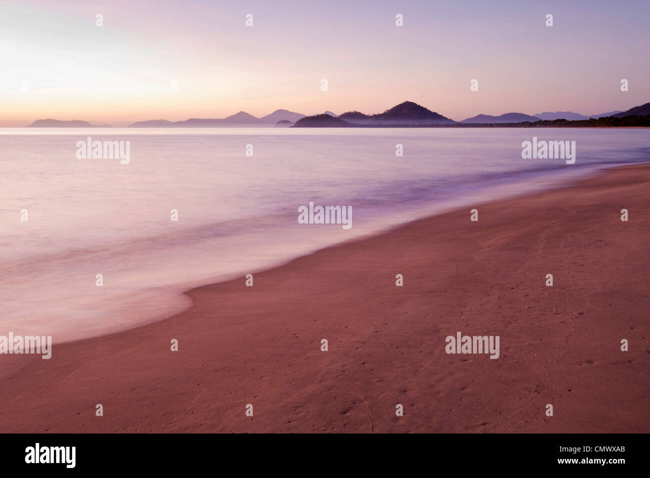 View along beach at dawn. Machans Beach, Cairns, Queensland, Australia - Stock Image