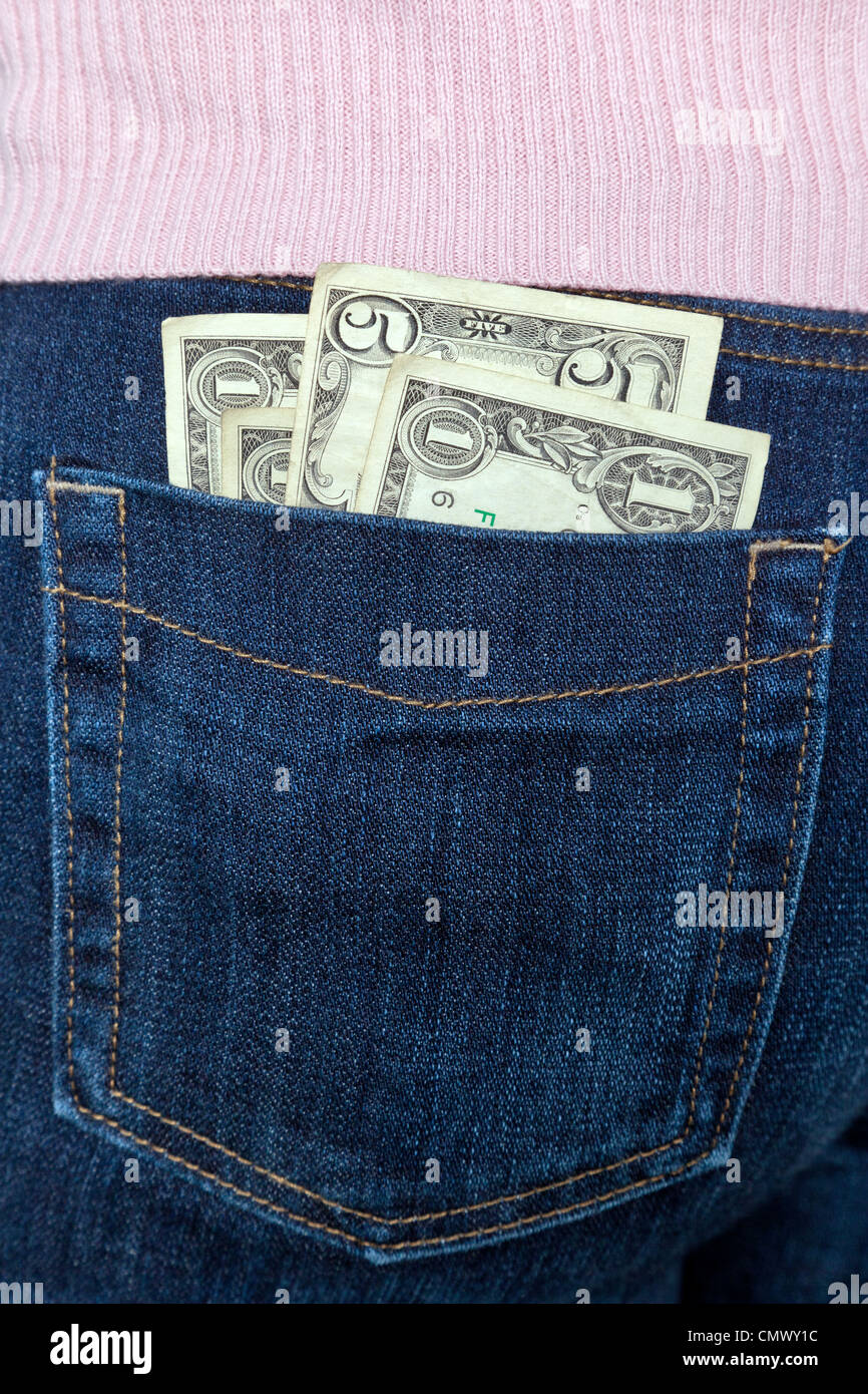 Photo of some US banknotes in the back pocket of a womans jeans. - Stock Image