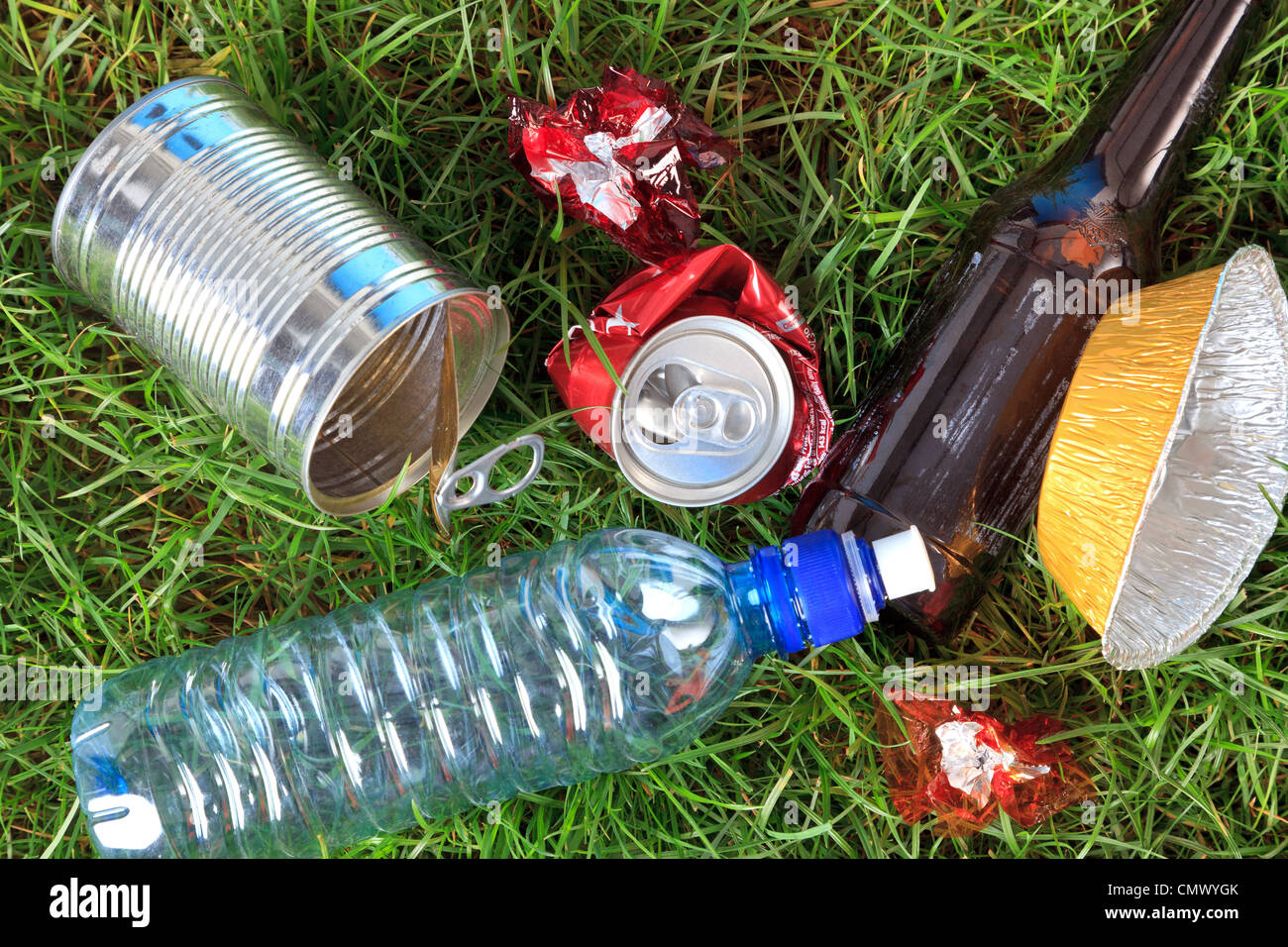 Photo of litter on grass, bottles, cans and wrappers. - Stock Image