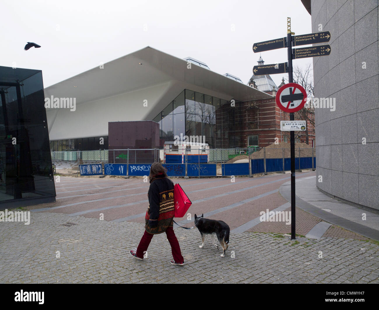 Woman with her dog walking on the Museumplein square in front of the new controversial Stedelijk Museum expansion - Stock Image