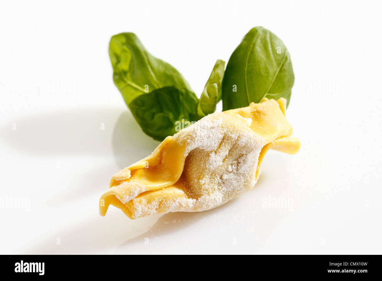 Candy shape pasta with riceflour and basil leaf on white background - Stock Image