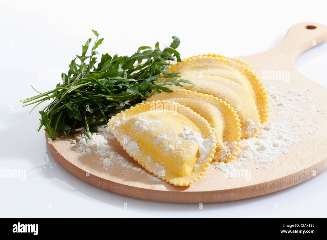 Crescent shape pasta with flour and rocket on chopping board - Stock Image
