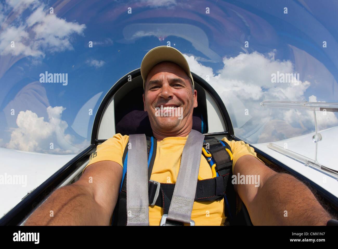 Germany, Bavaria, Bad Toelz, Mature man in glider, smiling, portrait - Stock Image
