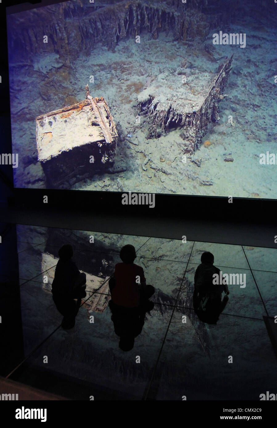 Children look at a projection showing an image of wreckage from the Titanic wreck on the seabed - Stock Image