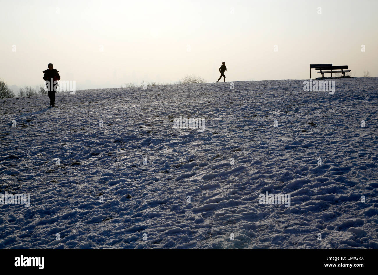 Walker and jogger taking in the view from the top of a snowy Parliament Hill, Hampstead Heath, London, UK - Stock Image