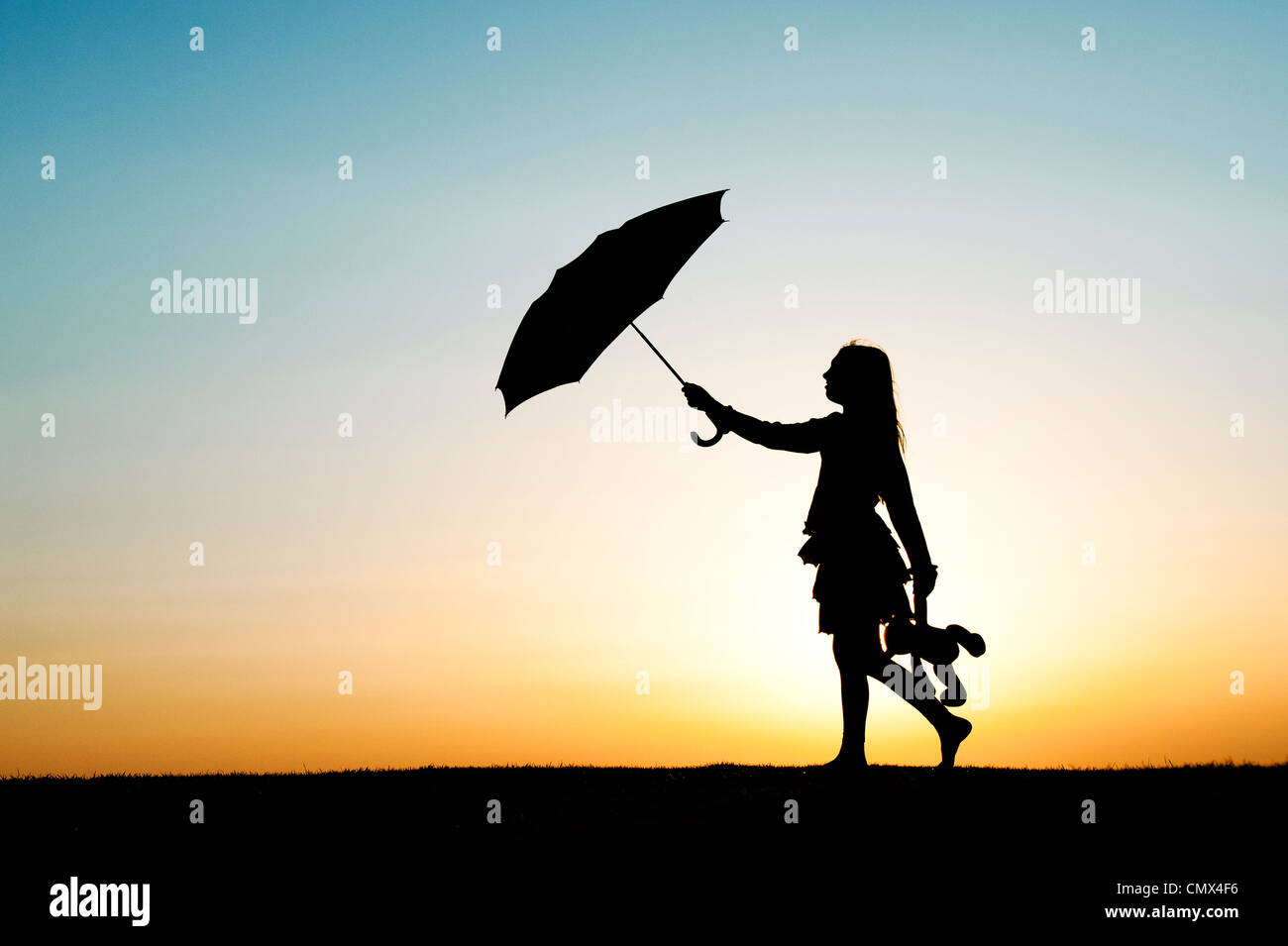 Young Girl walking with an umbrella and teddy bear at sunset. Silhouette.UK Stock Photo