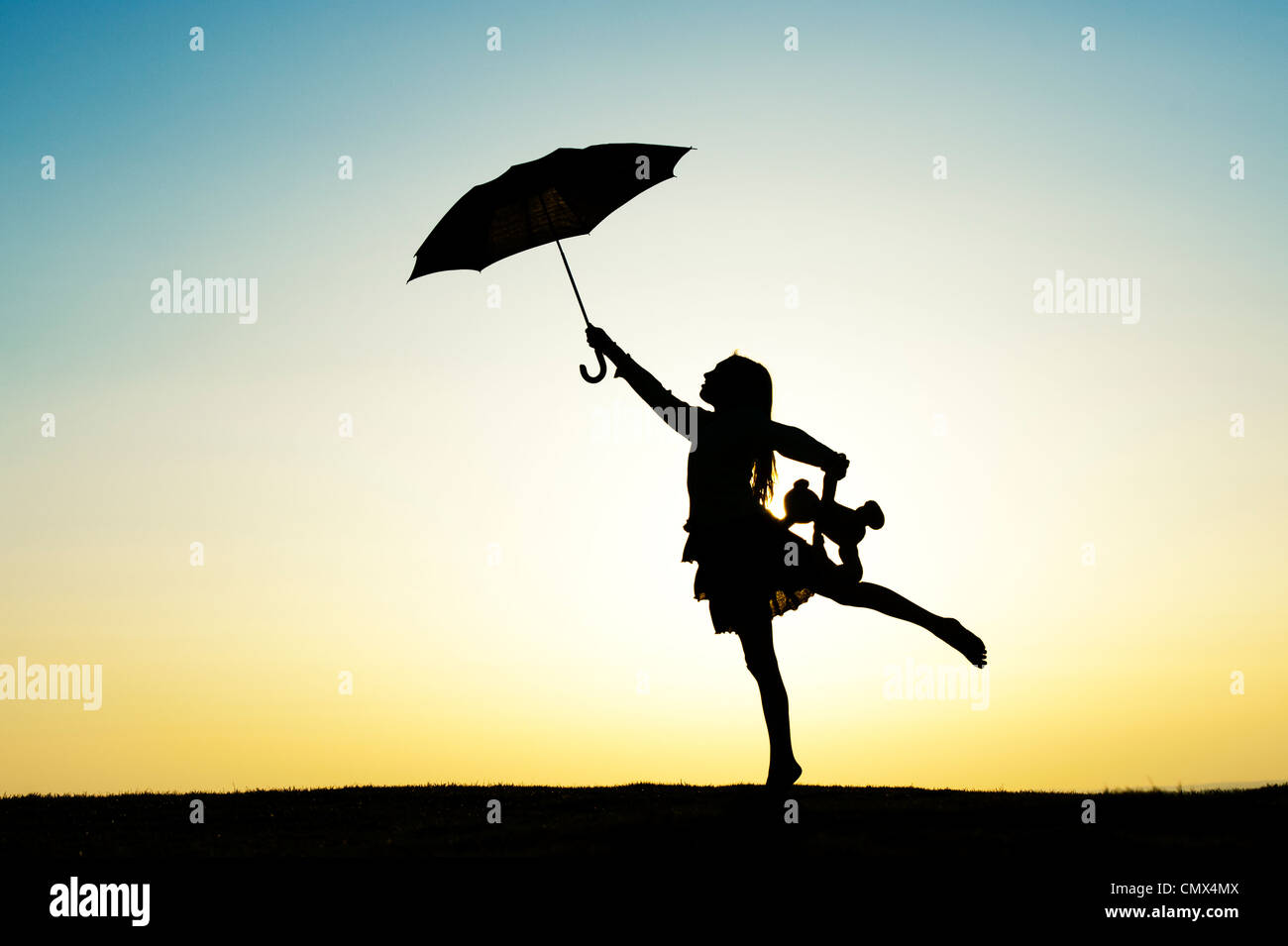 Young Girl jumping with an umbrella and teddy bear at sunset. Silhouette. UK Stock Photo
