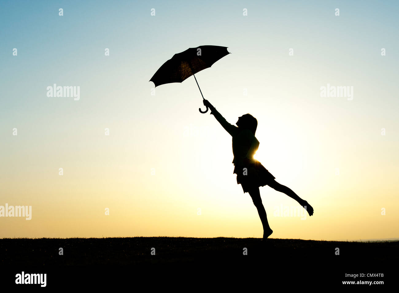 Young Girl jumping with an umbrella at sunset. Silhouette Stock Photo