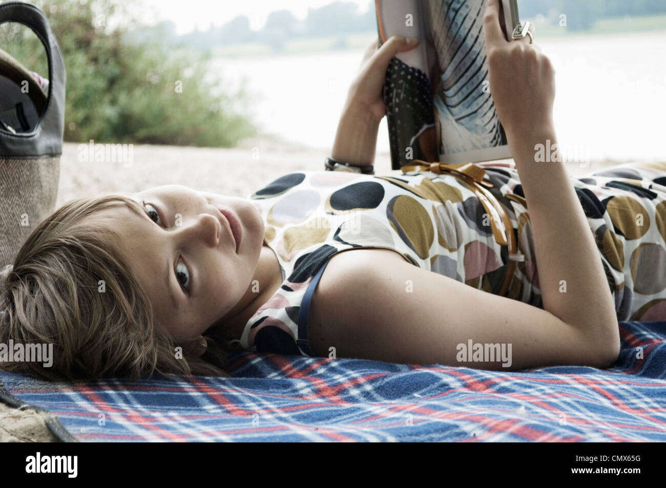 Germany, Rheinland, Young woman lying on blanket and reading book - Stock Image