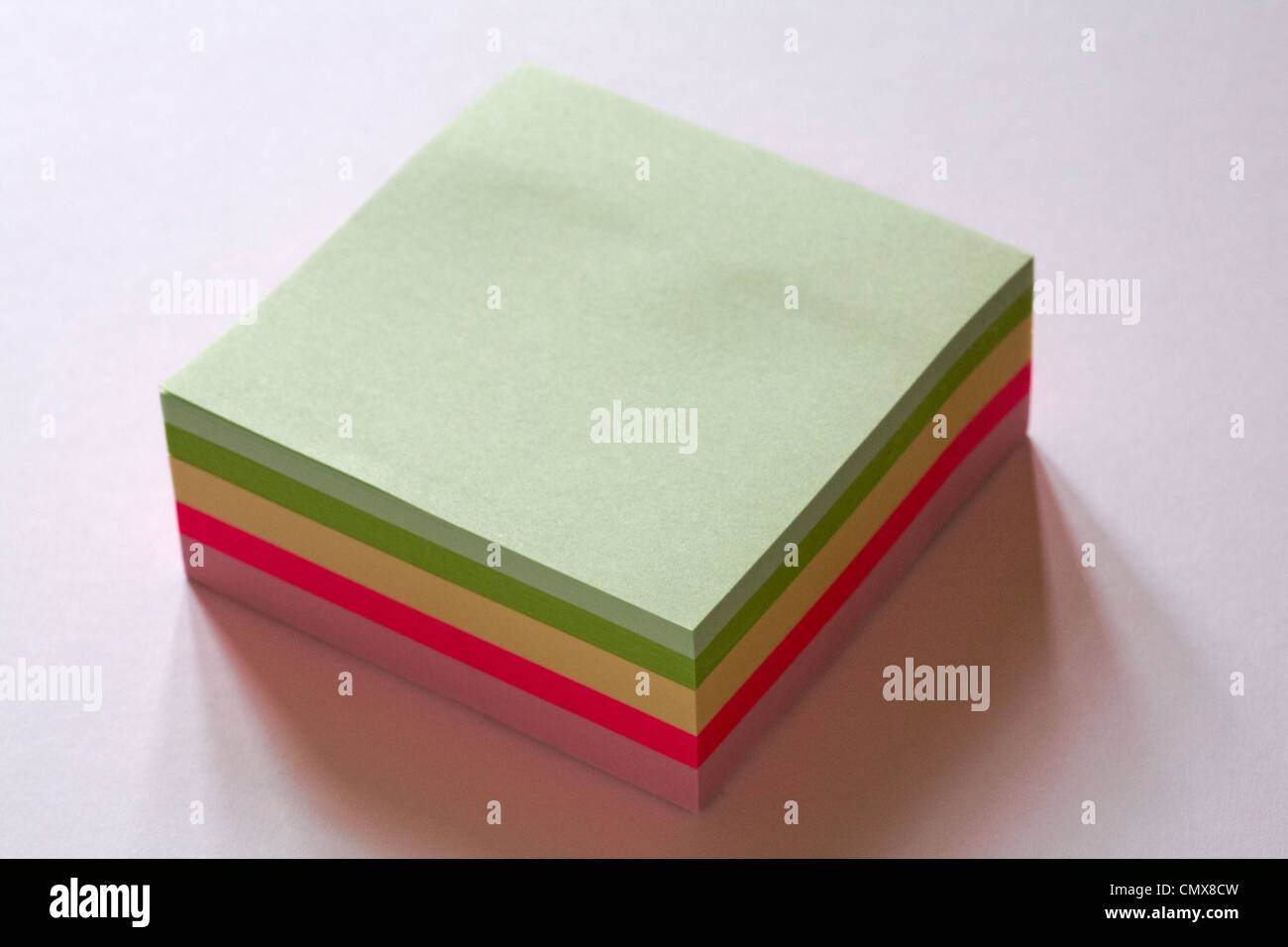 pad of blank multi coloured post it notes to add text to isolated on white background - Stock Image