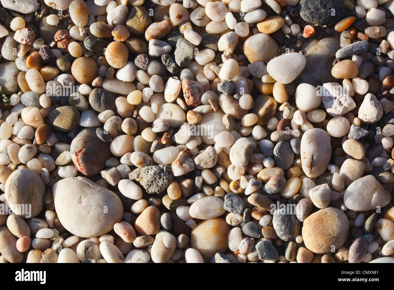 Pattern created by water-smoothed pebbles on beach. - Stock Image