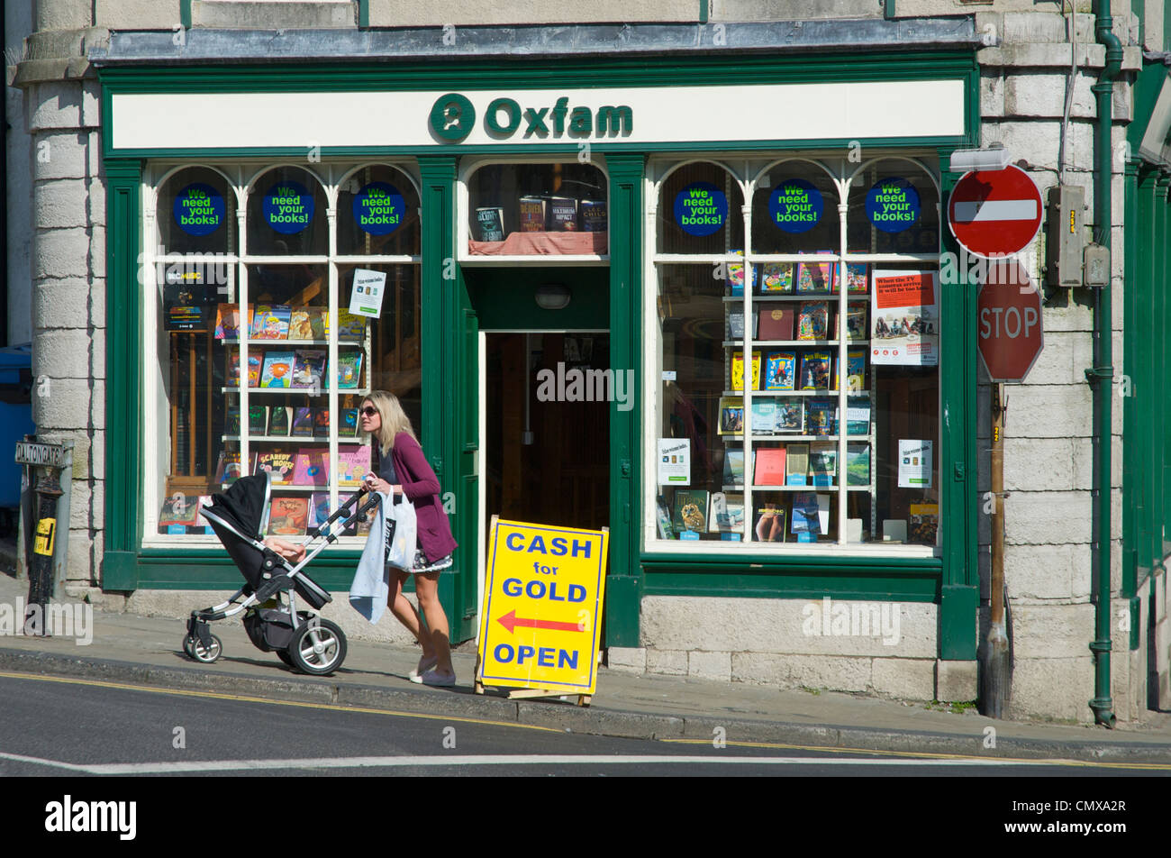 Young woman with pushchair outside Oxfam charity shop, in Ulverston, Cumbria, England UK Stock Photo