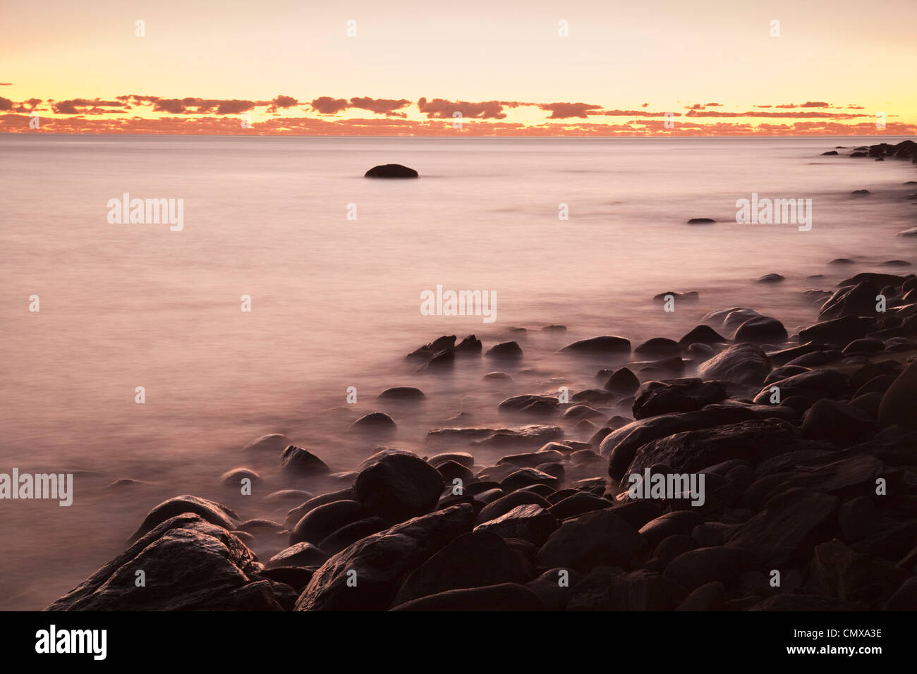 Dawn over the Coral Sea at Pebbly Beach, near Cairns, Queensland, Australia - Stock Image
