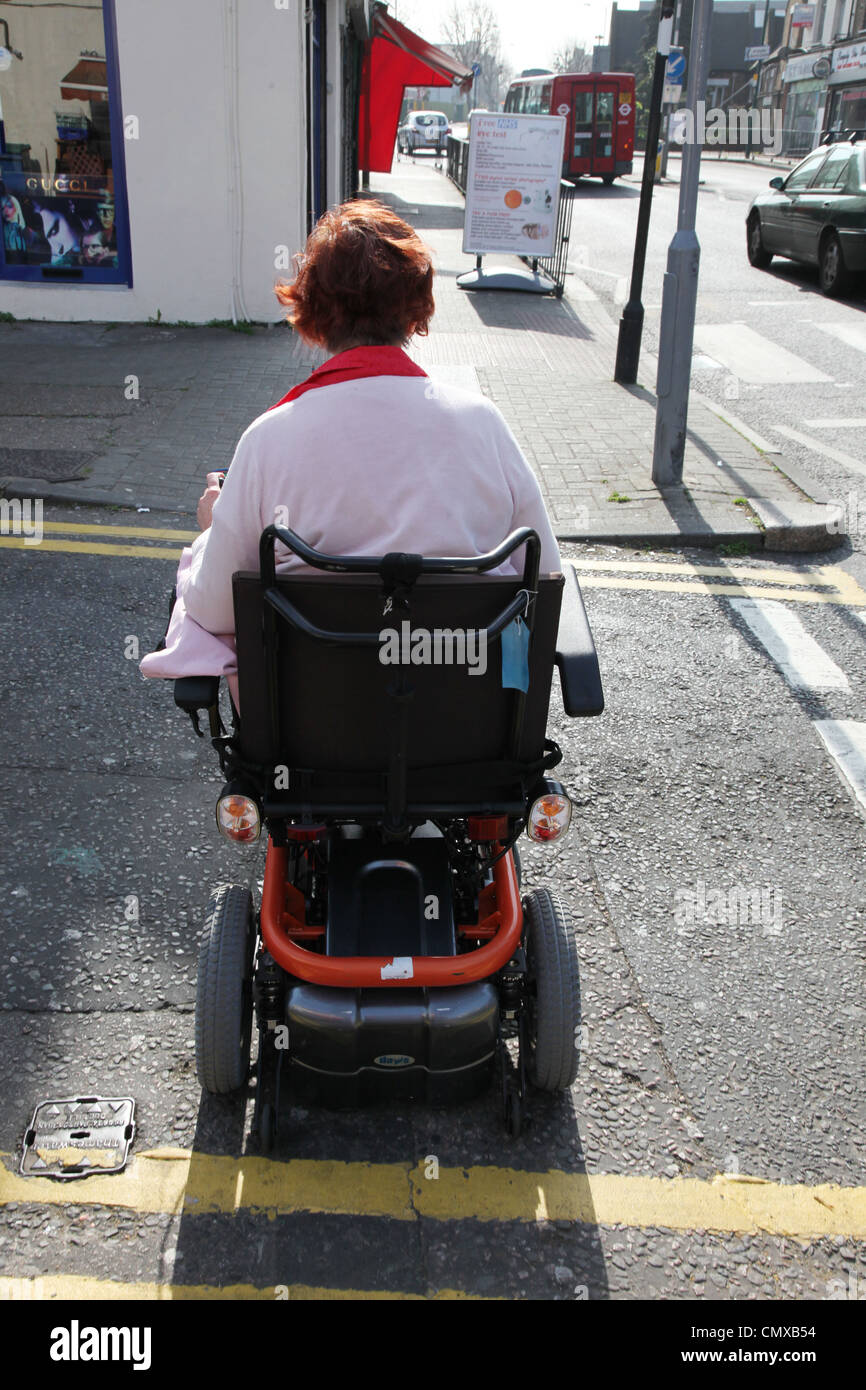 Electric wheelchair user driving on an an adapted pavement - Stock Image
