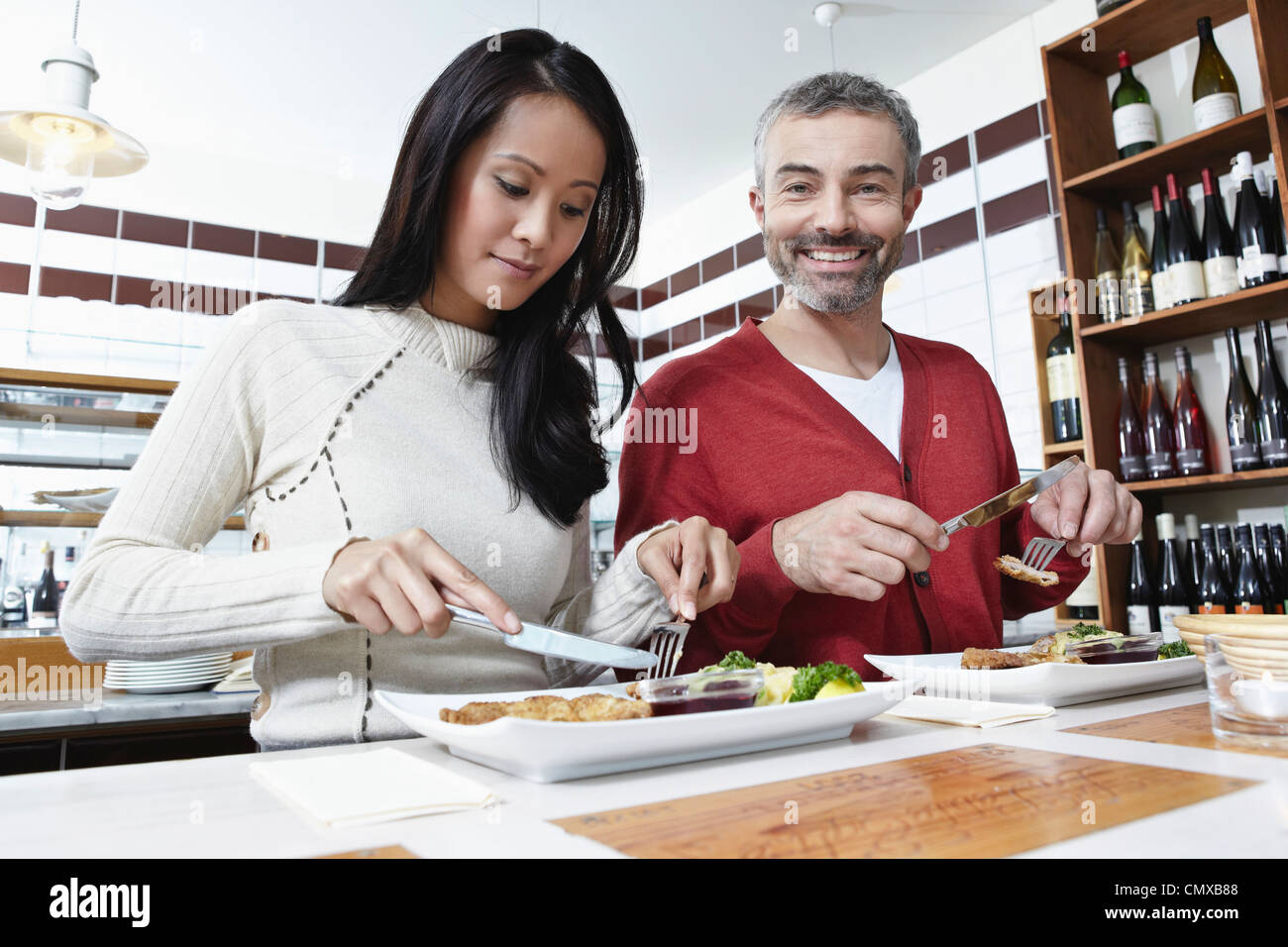 Germany, Cologne, Couple eating food in kitchen, smiling - Stock Image