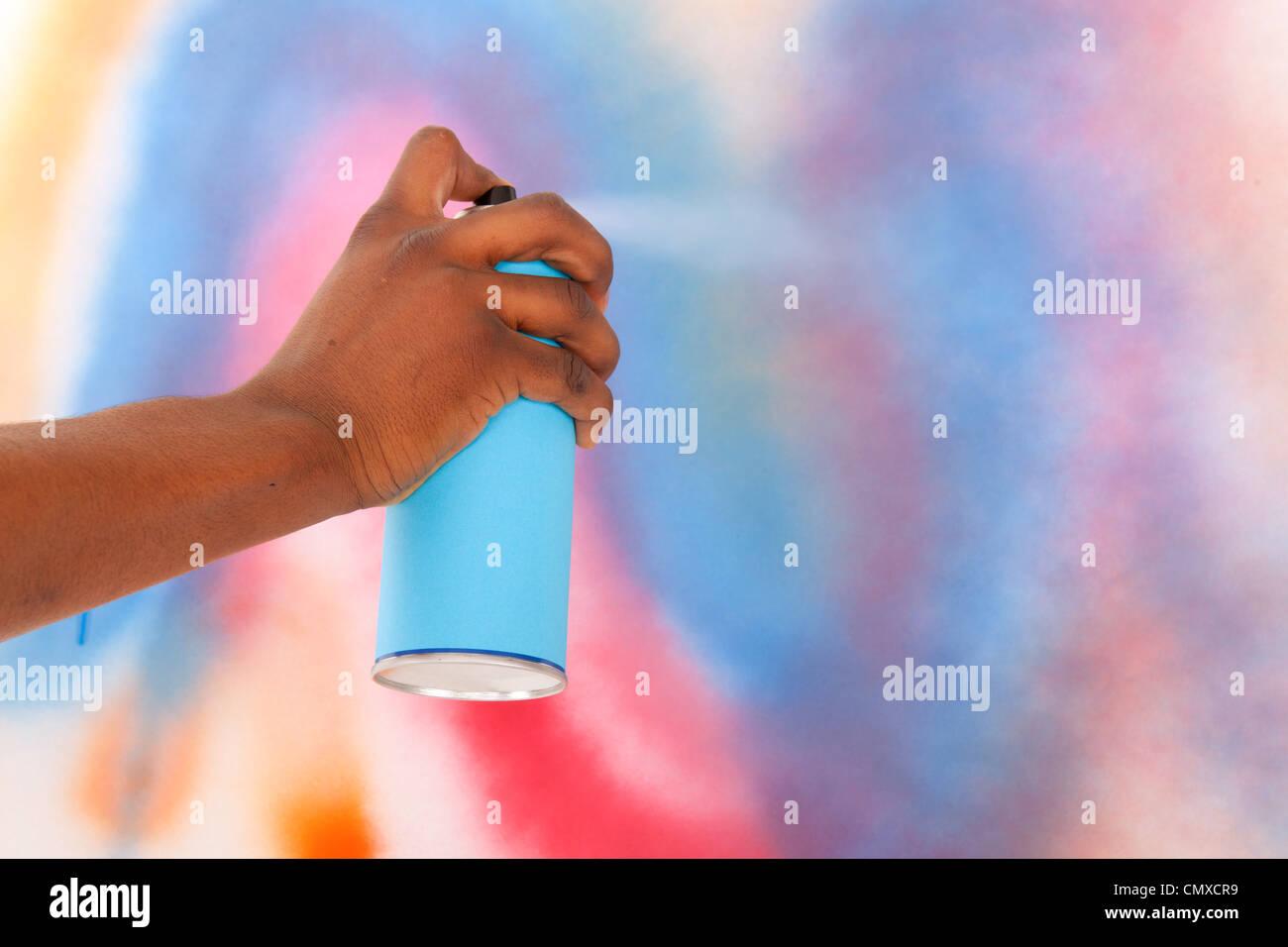 Hand is spraying with blue graffiti aerosol - Stock Image