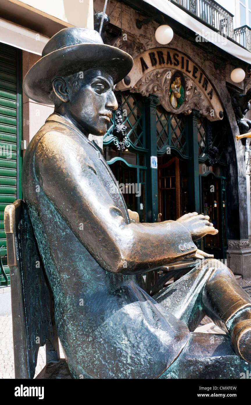 A bronze statue of Portuguese poet Fernando Pessoa sits outside the Café A Brasileira, Lisbon, Portugal - Stock Image
